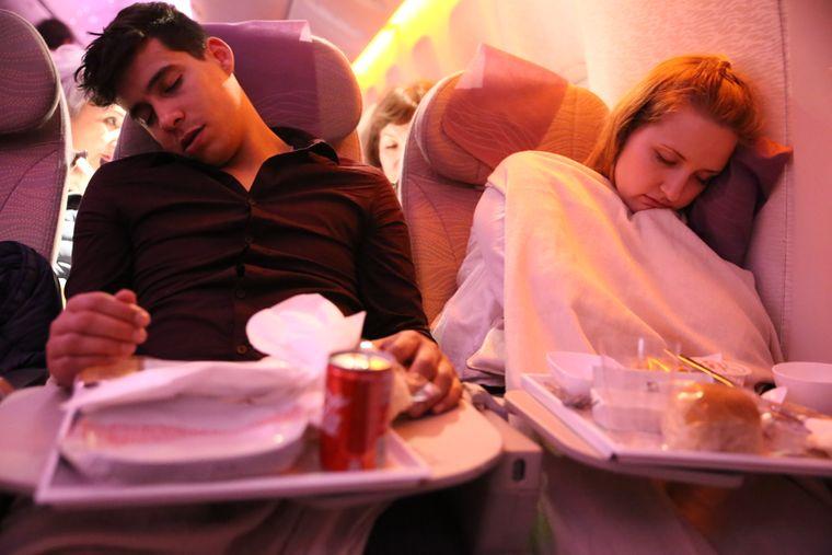 Mehr als zwölf Stunden im Flugzeug machen müde – das stellen auch Eduardo und Carina fest.