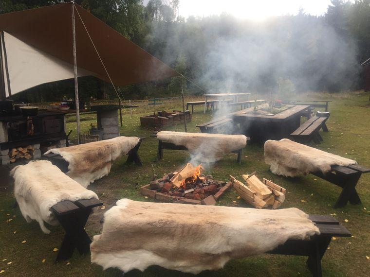 Auf der Farm von Bengt-Erik Hesse wärmt man sich am Lagerfeuer, und auch die auf der Holzbank ausgelegten weichen Felle aus Rentier helfen gegen kühle Temperaturen.
