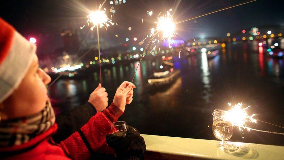Eine Frau begrüßt in der Silvesternacht das neue Jahr mit Wunderkerzen auf der Deutzer Brücke in Köln.