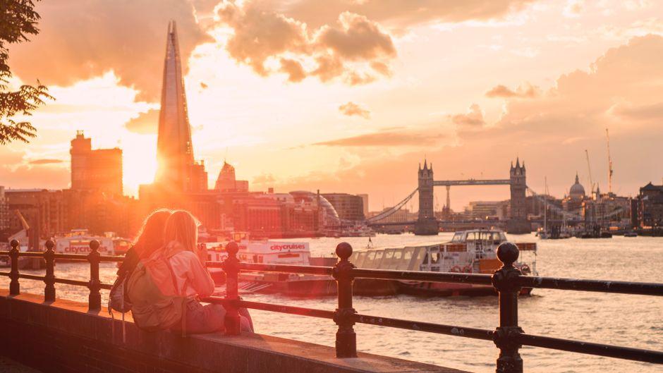 Zwei Touristen blicken auf die Themse in London.