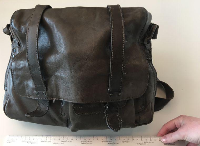 Handtasche mit Lineal liegt auf einem Tisch.