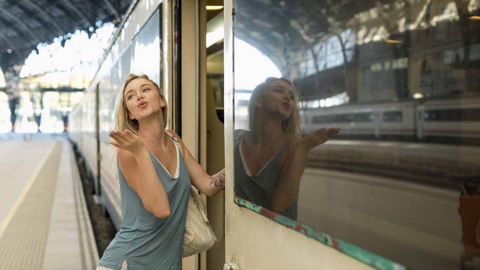 Eine Frau steigt in den Zug und verabschiedet sich mit einem Handkuss.