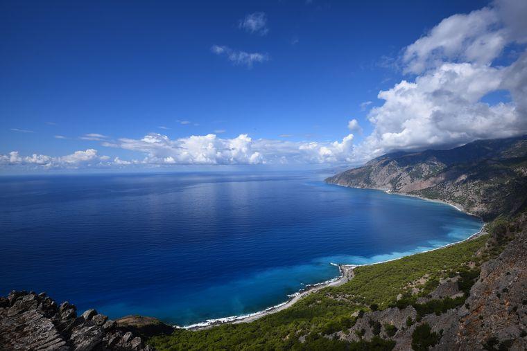 Blaues Meer brandet in eine grüne Bucht auf Kreta, Griechenland.