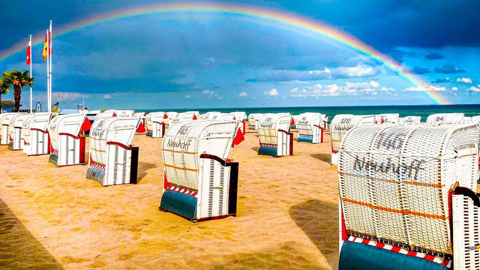 Ein Regenbogen ist durch die verregneten Wolken über dem Strand des Ostseeortes Grömitz zu sehen.