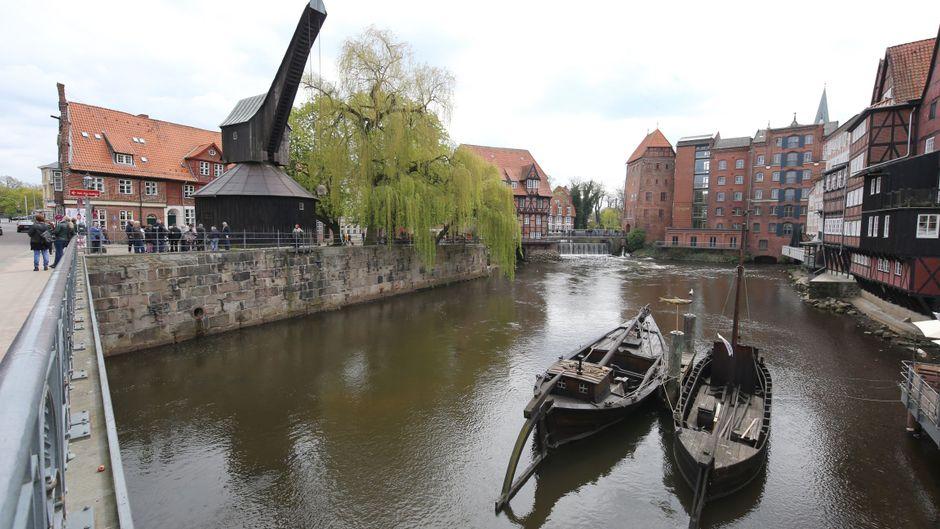 Am Stintmarkt fließt die Ilmenau vorbei – alte Kähne und ein mittelalterlicher Kran beleben das Bild.