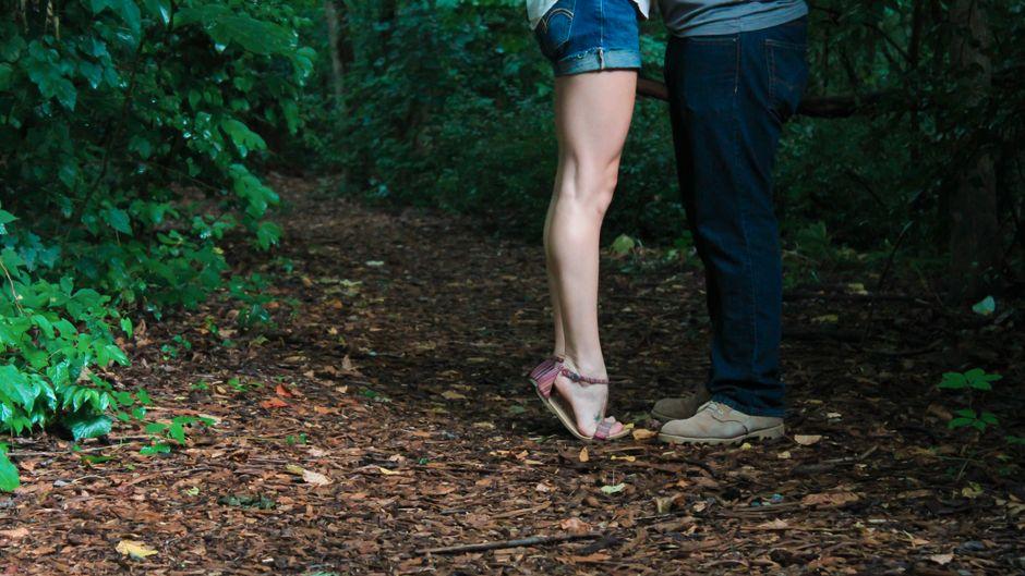 Pärchen küsst sich im Wald.