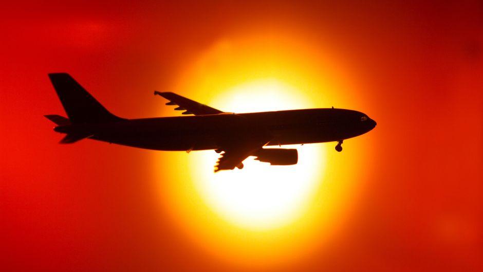 Flugzeug vor der untergehenden Sonne am Himmel.