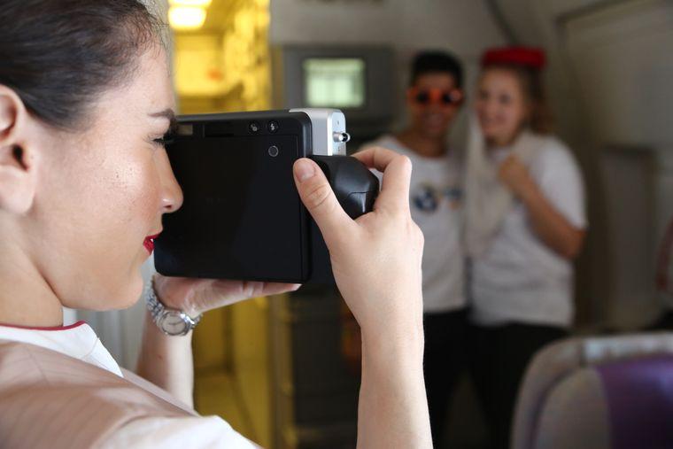 """… bis eine Stewardess auf beide aufmerksam wird – und den """"reisereportern 2018"""" ihre Kopfbedeckung für ein Erinnerungsfoto gibt."""