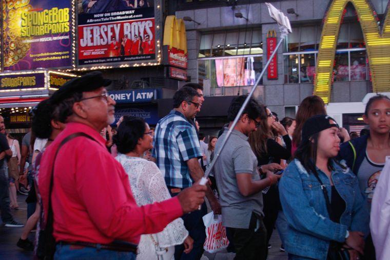 Ein Tourist macht mit seinem Handy am Times Square ein Selfie.