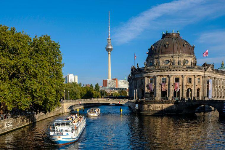 Blick auf die Spree mit einem Ausflugsboot und dem Fernsehturm sowie dem Bodemuseum im Hintergrund.