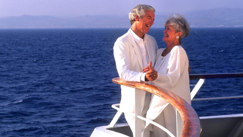 Ein Paar im Seniorenalter genießt die Meeresbrise auf einem Kreuzfahrtschiff.