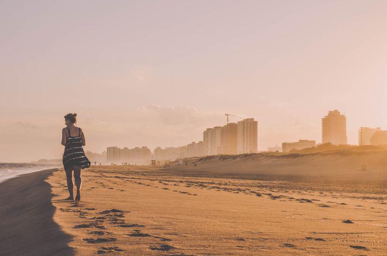 Eine Frau im Kleid spaziert am Strand von Punta del Este in Uruguay.