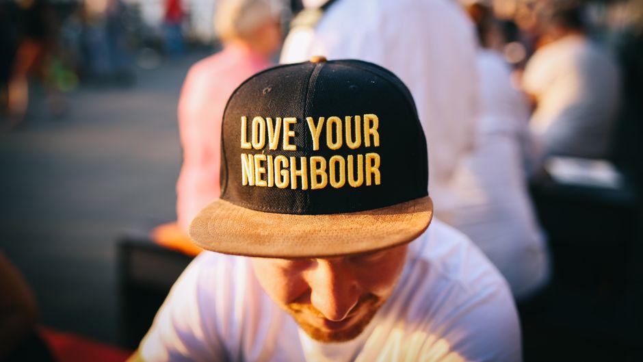 "Mann trägt eine Baseballcap mit dem Schriftzug ""Love your neighbour""."