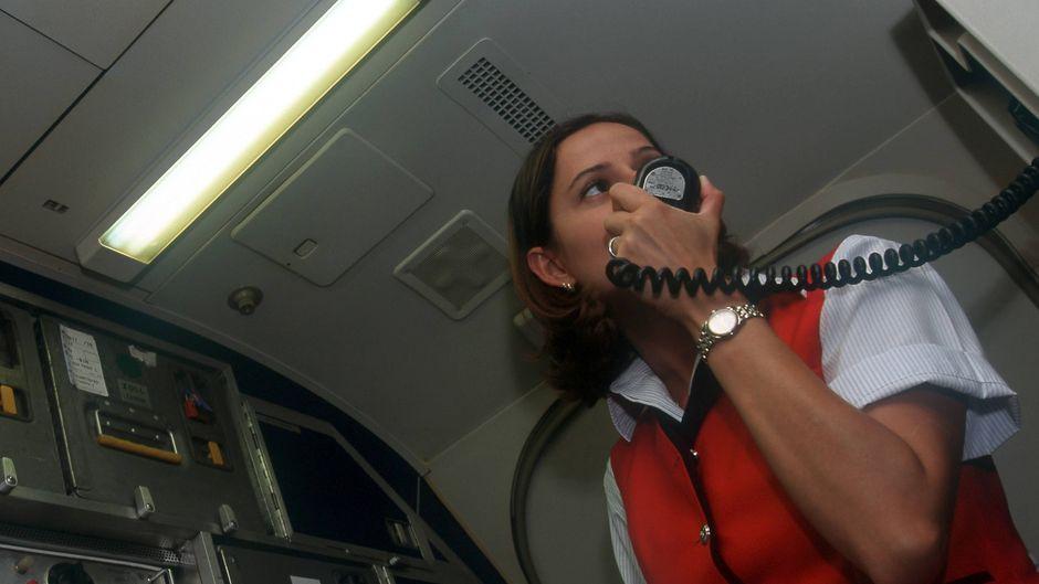 Eine Flugbegleiterin macht eine Durchsage.