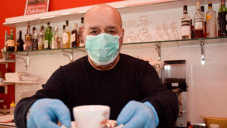 Ein Barista serviert in einem Mailänder Café Espresso mit Handschuhen und Mundschutz.