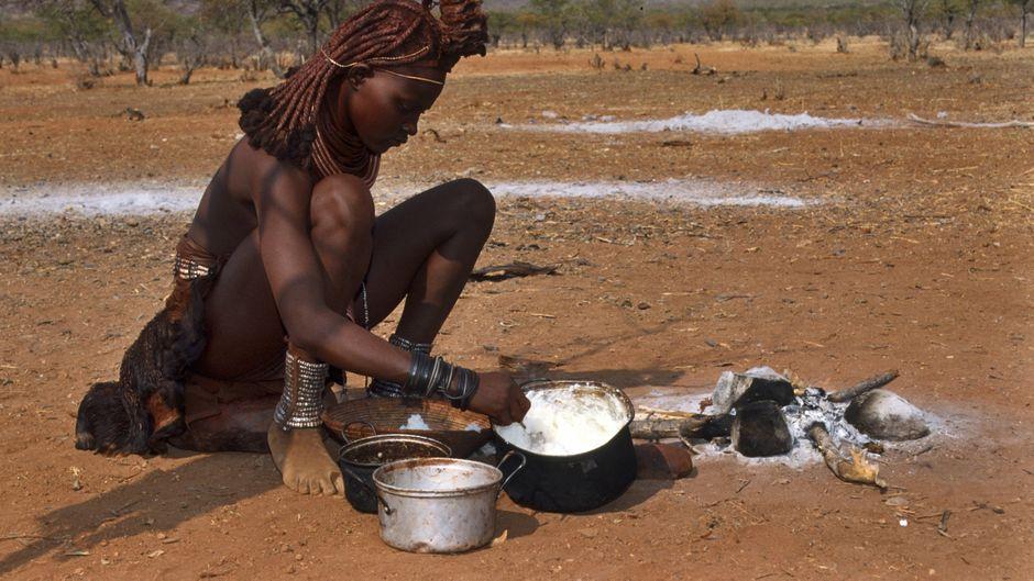 Eine Himba-Frau kocht ein traditionelles Gericht im Damaraland in Namibia.