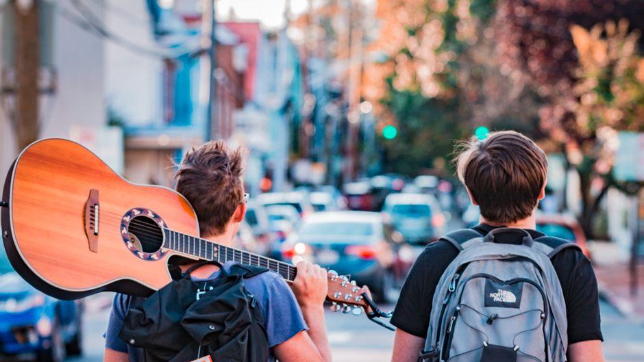 Zwei Urlauber mit Rucksäcken und Gitarre.