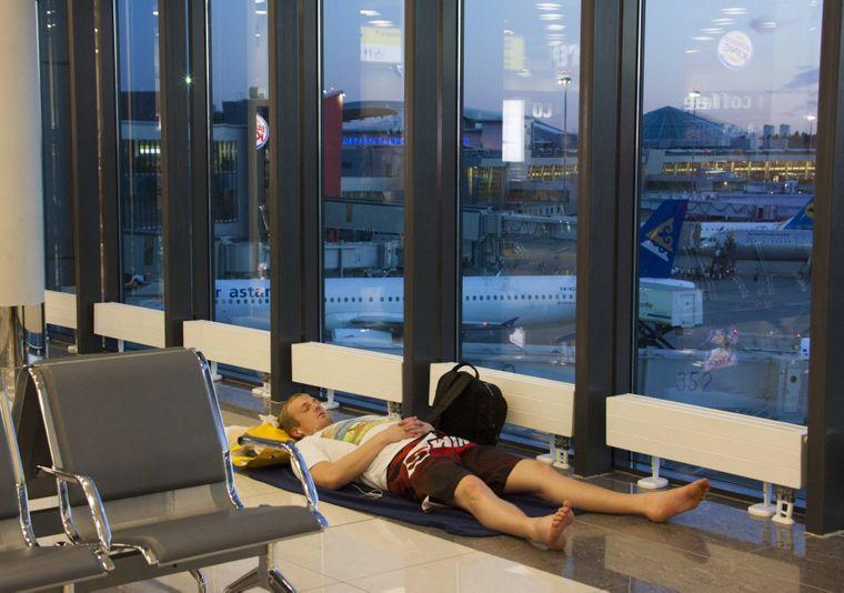 Eine Wartender schläft auf dem Boden des Flughafens in Moskau.