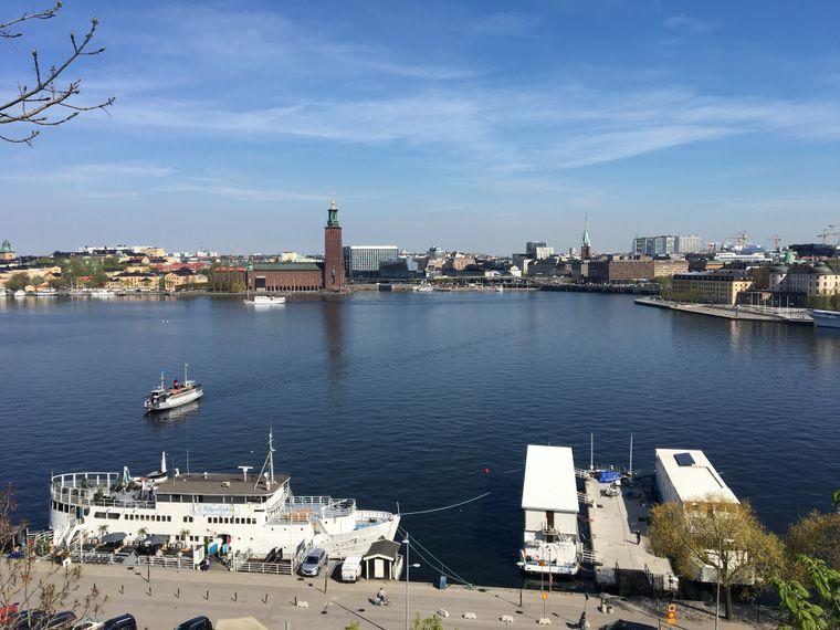 Die Boote sind zu Hotels umgebaut worden. Du blickt von dort zum Beispiel zum Stockholmer Rathaus mit dem Stadthausturm.