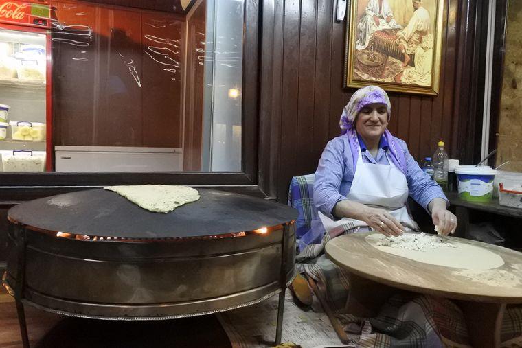 Eine Frau bereitet traditionell Fladenbrot mit Schafskäse-Füllung zu.