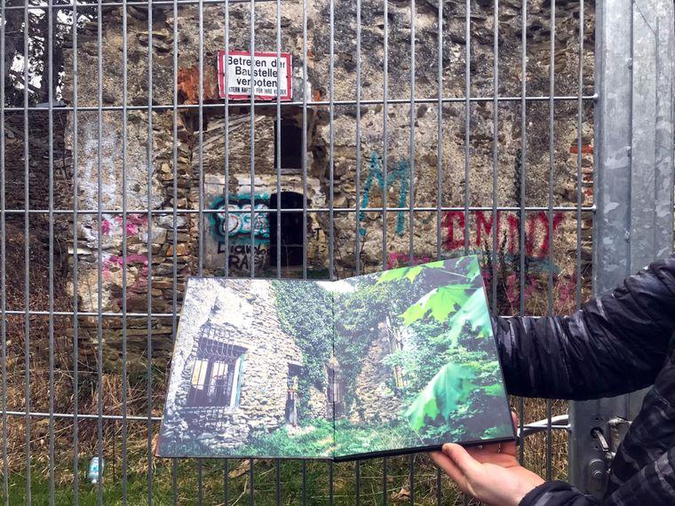 Buch mit Lost Places vor Zaun der Ruinenvilla.