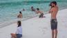 Männer fotografieren ihre Freundinnen an einem Strand in Thailand für Instagram.