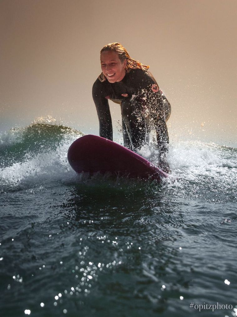 Michelle kniet auf dem Surfbrett im Atlantik.