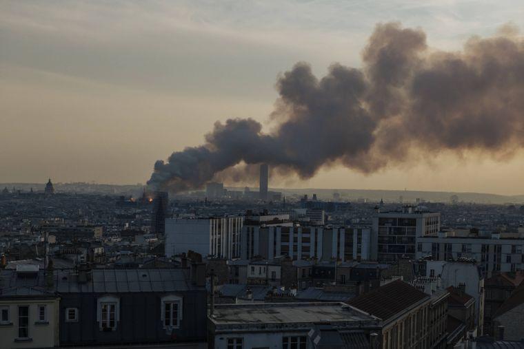Eine riesige gelbgraue Rauchsäule zieht über Paris.