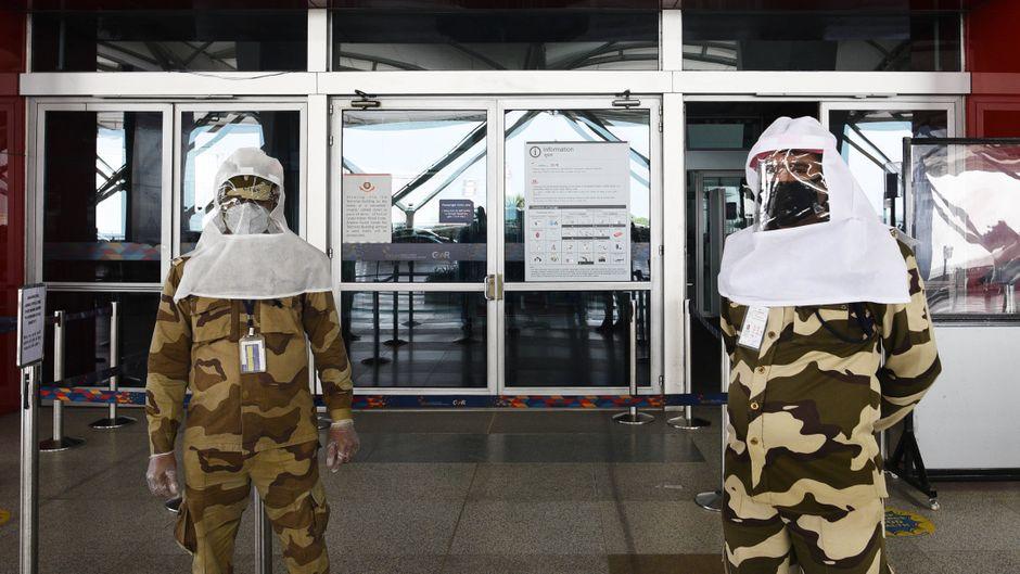Zwei Sicherheitsbeamte stehen am Eingang des Flughafens von Delhi in Indien.