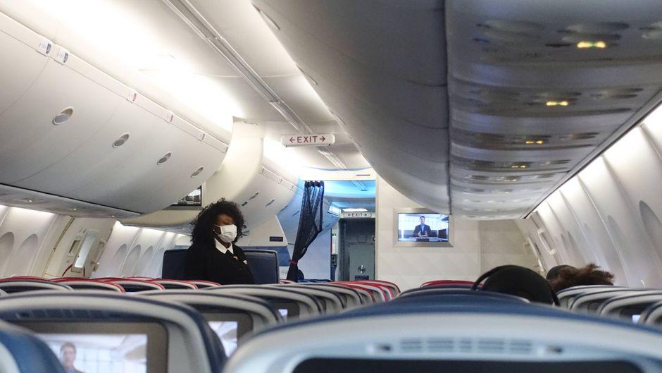 Diese Flugbegleiterin trägt einen Mund-Nasen-Schutz. Wie sieht das Fliegen nach der Corona-Krise aus?