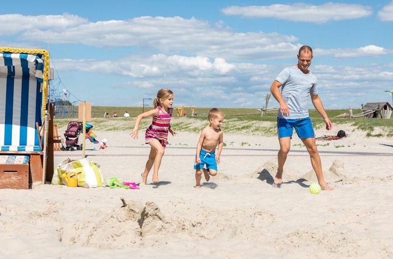 Ein Vater spielt mit seinen beiden Kindern Ball im Sand