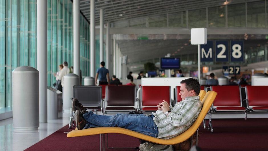 Die Wartezeit am Flughafen verbringen viele Passagiere am Handy. (Symbolfoto)