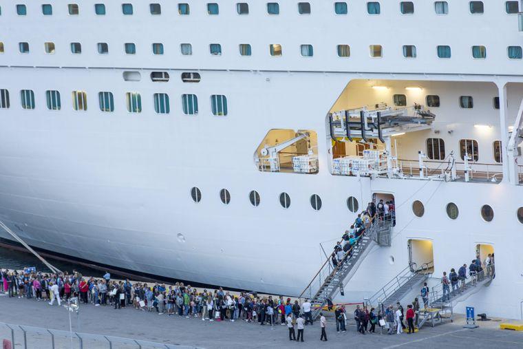 Passagiere checken in ein Kreuzfahrtschiff ein.