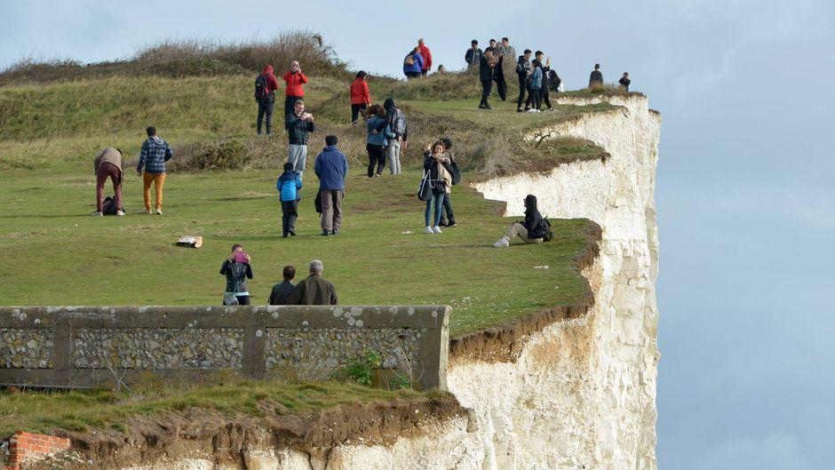 Touristen tummeln sich an den als Seven Sisters bekannten Klippen in East Sussex, rund zwei Stunden südlich von London, England.
