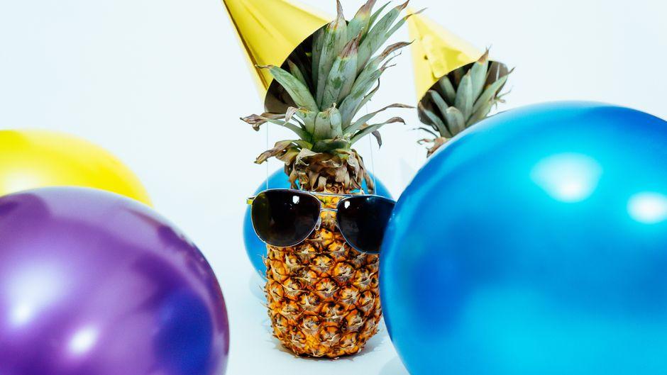 Ananas mit Sonnenbrille und Partyhut zwischen Luftballons