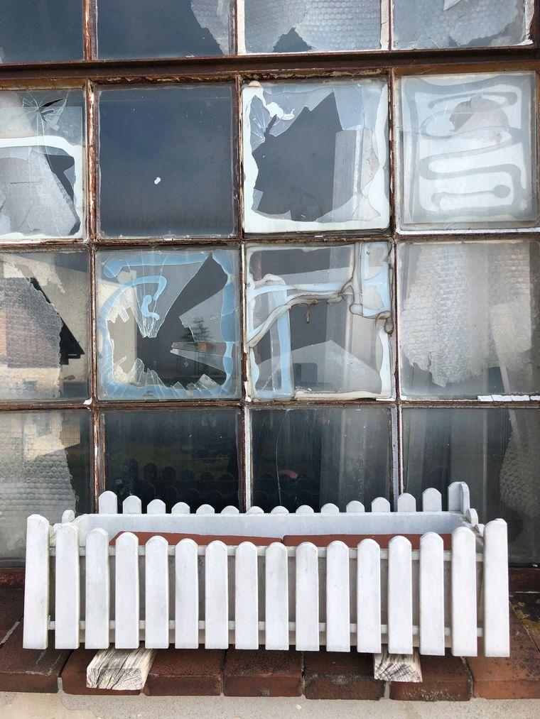 Eigenwillige Idylle: Blumenkasten vor einem teils zerstörten Fenster eines der im Verfallen begriffenen Gebäude.