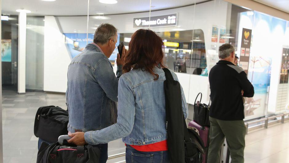 Urlauber stehen am Flughafen Hannover-Langenhagen vor Thomas Cook.