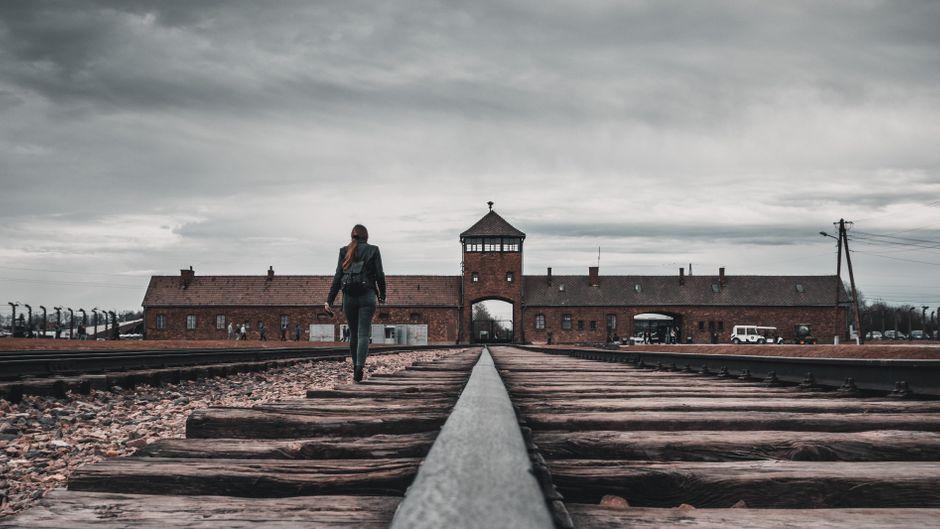 Auch diese Frau geht für ein Foto auf den Gleisen im ehemaligen KZ.