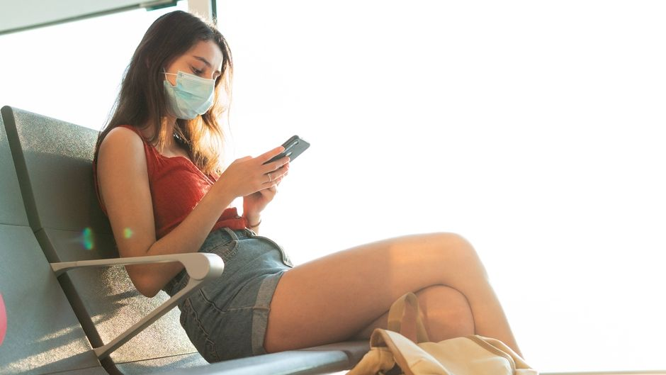 Eine Frau mit Mundschutz sitzt am Flughafen und bedient ihr Smartphone. Einige Apps erleichtern das Reisen. (Symbolfoto)