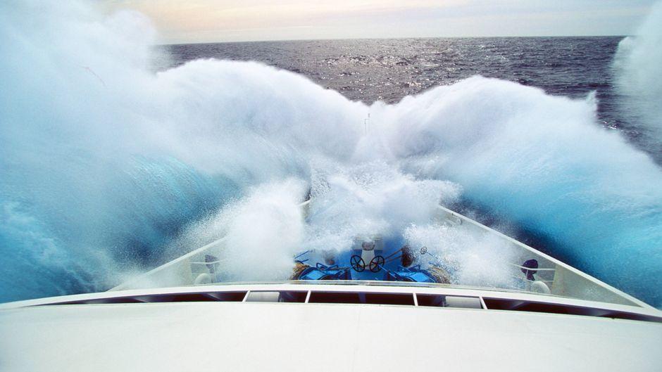 Eine Welle schlägt über Schiffsbug eines Kreuzfahrtschiffes.