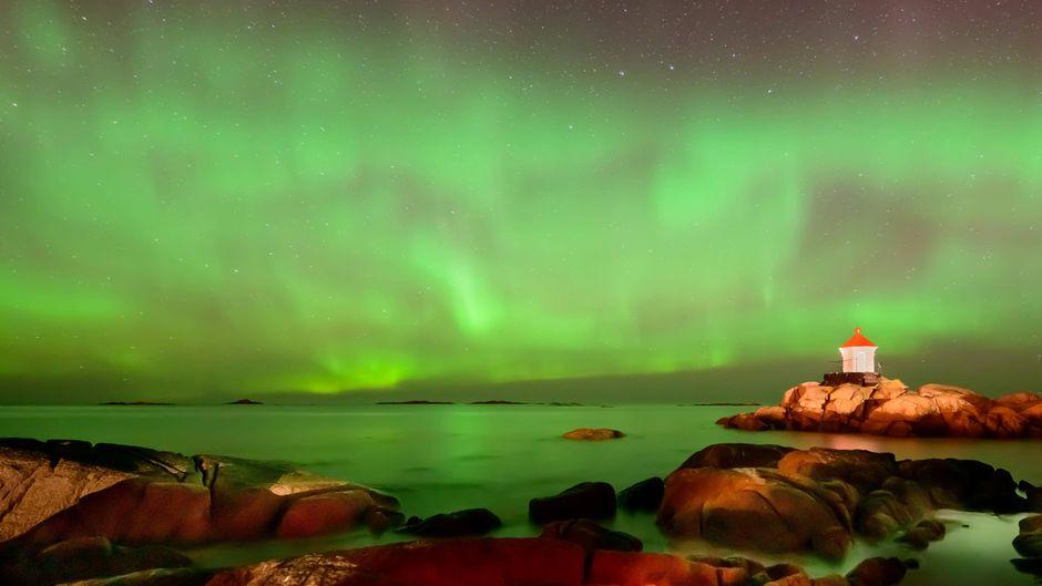 Grünes Nordlicht hinter einem Leuchtturm in Eggum auf den Lofoten.