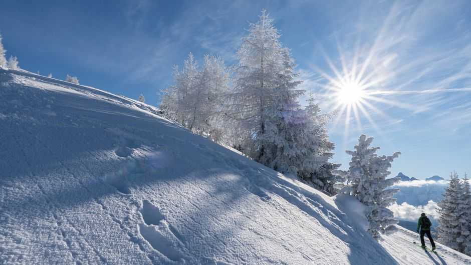 Ein Skitourengeher steigt einen verschneiten Berg bei strahlendem Sonnenschein hinauf.