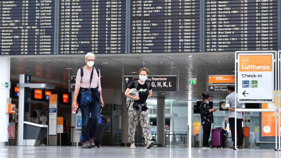 Reisende mit Gepäck und Mundschutz am Flughafen München. Ankommende Passagiere bekommen dort ab sofort einen kostenlosen Corona-Test.
