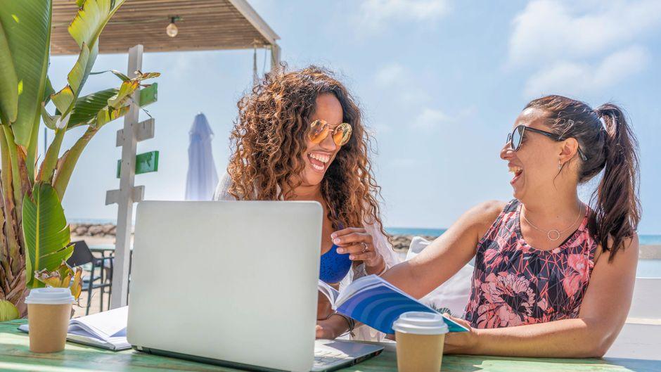 Zwei Frauen reden und trinken Kaffee im Urlaub.