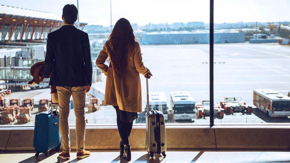 """Geschäftsreisende stehen am Flughafen und schauen aufs Rollfeld. In welchen Ländern sind die Risiken 2021 am höchsten? Das zeigt die """"Travel Risk Map""""."""