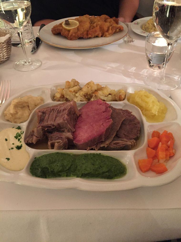 Ein Tafelspitz liegt mit weiteren Fleischsorten und Beilagen auf einem Teller.