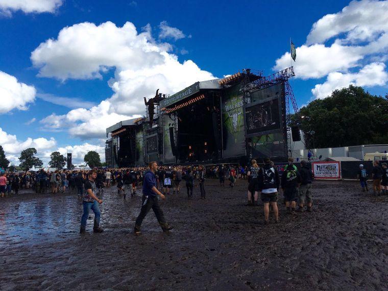 Festivalbesucher waten beim Wacken Open Air 2016 durch Matsch.