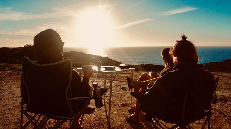 Felix, Tim und Ina genießen das Abendessen beim Sonnenuntergang mit Blick aufs Meer.