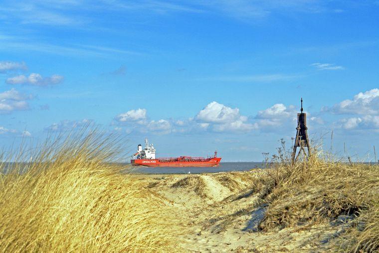 Ein Frachtschiff schippert vor Cuxhaven über die Nordsee. Rechts im Bild: die Kugelbake an der Elbmündung.