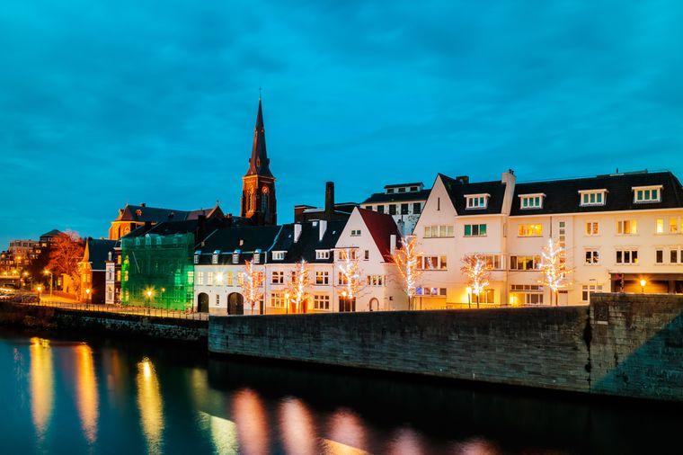 Maastricht in wunderschönem Licht am Abend mit der Maas im Vordergrund.